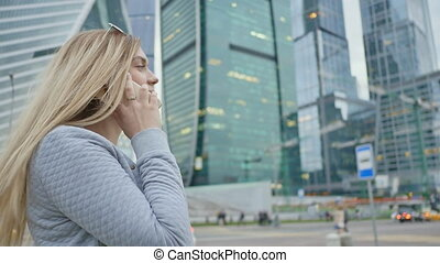 A blonde girl is talking on the phone in the background of skyscrapers and high-rise buildings in the city center.