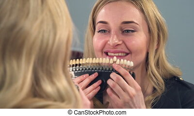 A blonde girl looks front of the mirror at the result of...