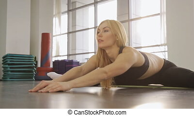 A blonde woman athlete doing stretching in the gym. while in the splits she stretches forward.