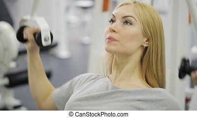 A blonde woman athlete, trains on the back, the latissimus dorsi, blades, rear delts shoulder in the gym, using rowing machine.