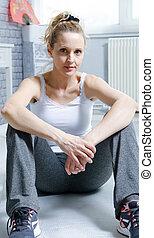 blonde woman in sportswear sitting on the floor