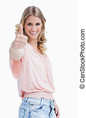 A blonde woman with her thumb up smiling at the camera