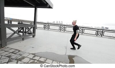 A blonde young teenager man jumps street acrobatic parkour in promenade, slow-motion