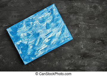 blue and white painted canvas on black wall