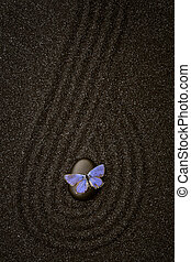 A blue butterfly on a zen stone  with a wave lines in the black grain sand