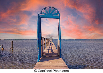 A blue door in the Caribbean Sea on the island of Roatan at sunset. Honduras