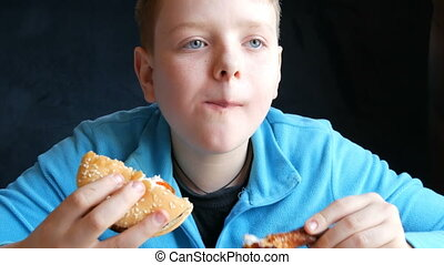 A blue-eyed handsome boy teenager alternately eats a hamburger and fatty fried chicken wings in a fast food restaurant and looks at a camera