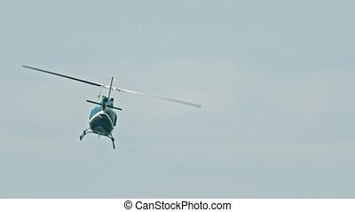 A blue helicopter flying in the sky at overcast weather. Mid...