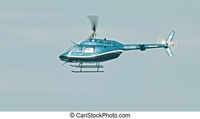 A blue helicopter flying in the sky