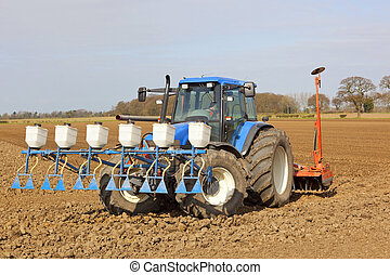 a blue tractor applying granular pesticide and cultivating in springtime