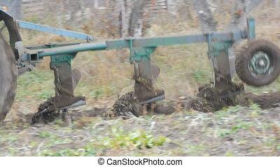 A blue tractor plows black soil in deep autumn. Winter ground preparation