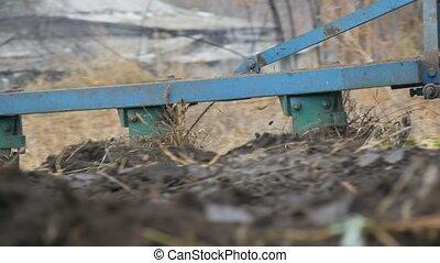A blue tractor plows black soil in deep autumn. Winter...