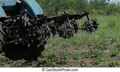 A blue tractor with a metallic harrow moves back in late...