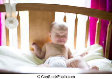 blurred image of a crying baby girl in bedroom