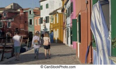 A blurred scenery of italian Burano with walking tourists