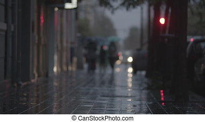 A blurred view of a paved street on a rainy evening