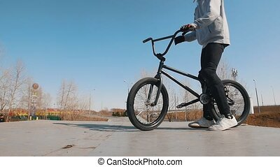 A bmx rider in grey hoodie riding in the skatepark and...