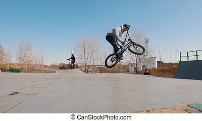 A bmx rider in grey hoodie riding in the skatepark. Mid shot