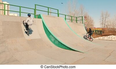 A bmx riders training their skills in the skatepark on a...