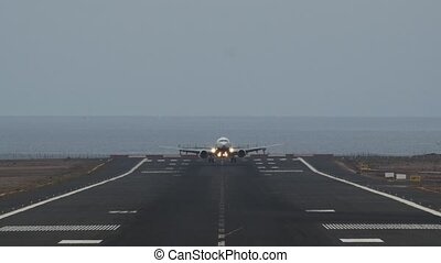 A frontal shot of an airport landing strip with a plane, going down, landing and riding towards the camera