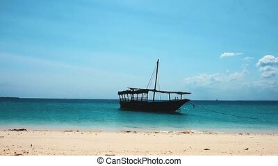 A boat anhcored near the sand coast - A boat anchored in...