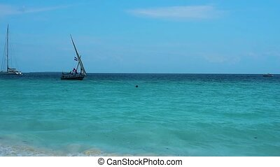 A boat floats in shallow water - A small sailing ship sails...