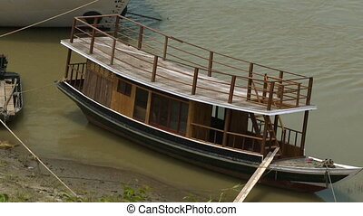 A boat on a river bank - A close up shot of a wooden boat...