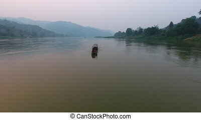 A boat sailing on a river - A wide shot of a boat carrying...