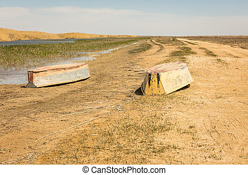 A boat turned upside down. Rowing boats in the reeds. Wooden boat on a grassy lake shore on a summer day. Aral sea, Kazakhstan