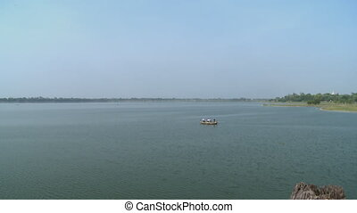 A boatman paddling a boat that has passengers - An ...