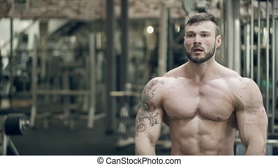 A bodybuilder with a tattoo makes a pose with a double bicep...