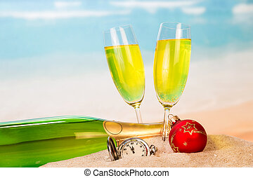 A bottle and two glasses with champagne, clock, Christmas ball in the sand against the background of the sea.