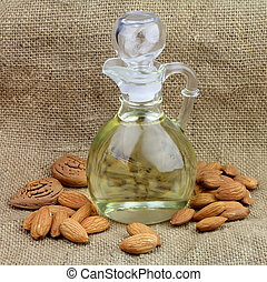 A bottle of almond oil with nuts on the linen texture