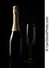A bottle of champagne and a glass on a black background.
