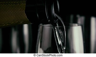 A bottle of champagne is pouring into a glass. Slow motion