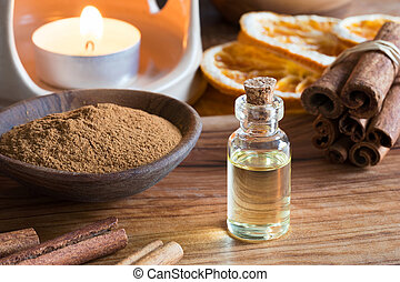 A bottle of cinnamon essential oil with cinnamon sticks