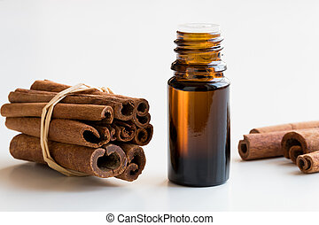 A bottle of cinnamon essential oil with cinnamon sticks on white background