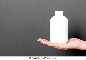 A bottle of cosmetic product in a female hand at black background with copy space