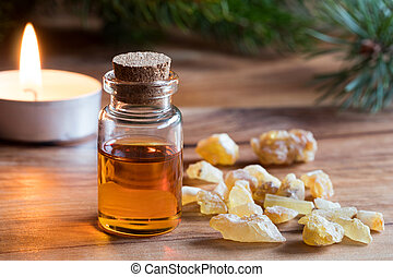 A bottle of frankincense essential oil with frankincense resin and a candle in the background