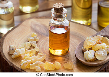 A bottle of frankincense essential oil with frankincense resin on a wooden table