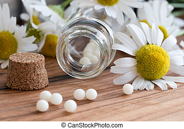 A bottle of homeopathic pills with chamomile flowers - A...