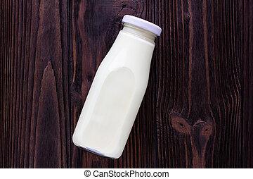 A bottle of milk on wooden background.