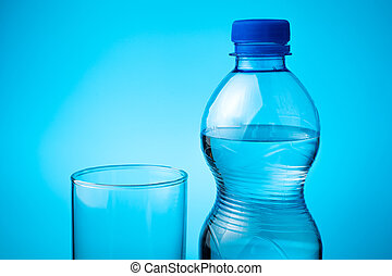 A bottle of mineral water and an empty glass on a blue background.