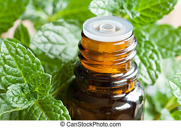 A bottle of peppermint essential oil with fresh mint leaves