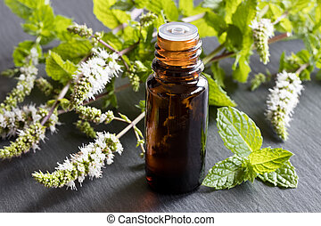 A bottle of peppermint essential oil with peppermint leaves