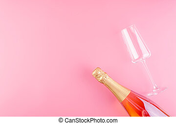 A bottle of pink champagne and an empty glass on a pink pastel background.
