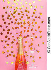 A bottle of pink champagne and an empty glass surrounded by gold confetti stars on a pink pastel background.