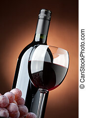 A bottle of red wine and a wine glass closeup - Bottom view ...