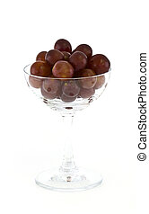 A bottle of red wine with glass and grapes