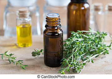 A bottle of thyme essential oil with fresh thyme twigs